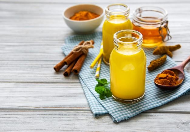 Leite dourado com canela, cúrcuma, gengibre e mel sobre superfície de madeira branca