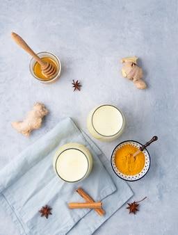 Leite dourado com cúrcuma e mel no fundo azul