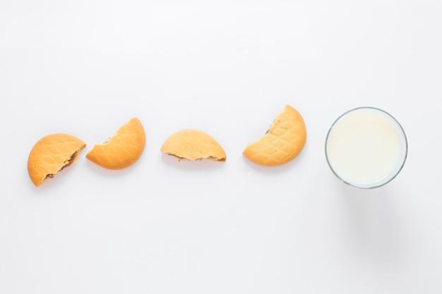 Leite e biscoitos dispostos em uma fileira para café da manhã sobre fundo branco