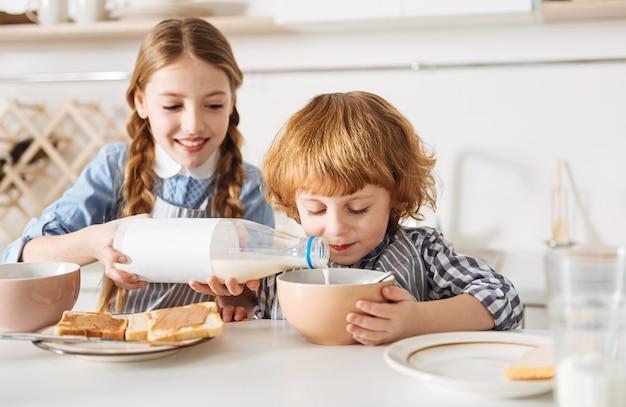 Leite e chocolate. criança alegre e entusiasmada fazendo seus irmãos saborearem cereais com um gosto celestial, adicionando um pouco de leite a eles