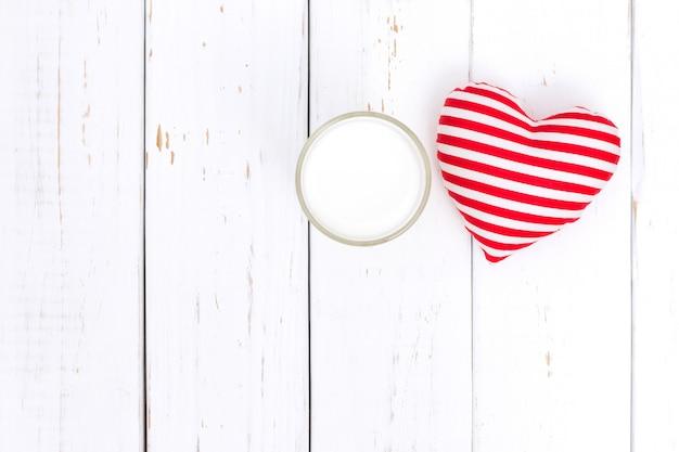 Leite e coração vermelho na mesa de madeira branca