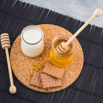 Leite e mel potes com biscoitos e pólen de abelha na montanha-russa de cortiça