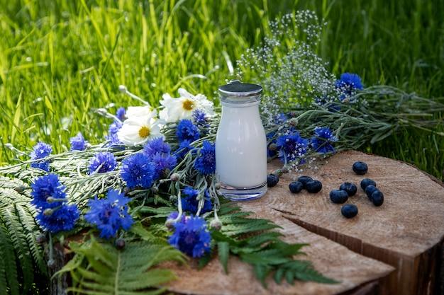 Leite e mirtilos no corte de madeira com verão wildflower-samambaia, flores azuis e flores cosmea