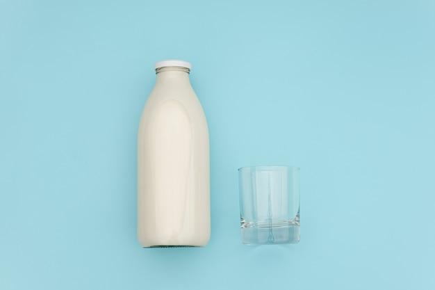 Leite em frasco de vidro e copo vazio no azul