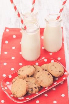 Leite em garrafa com canudo de papel com biscoitos