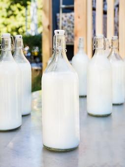 Leite em grandes garrafas de vidro na mesa cinza