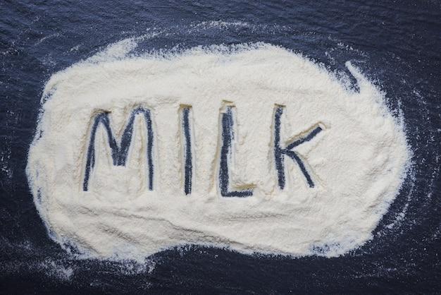 Leite em pó em fundo escuro - leite em pó texto vista superior alimento saudável corpo de proteína ou para o conceito de bebê