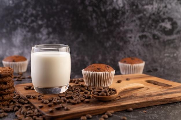Leite em um copo, completo com grãos de café, cupcakes, bananas e biscoitos em uma placa de madeira.