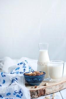 Leite em um copo e em uma garrafa, muesli em um copo azul e abacaxi e toalha de mesa com flores azuis