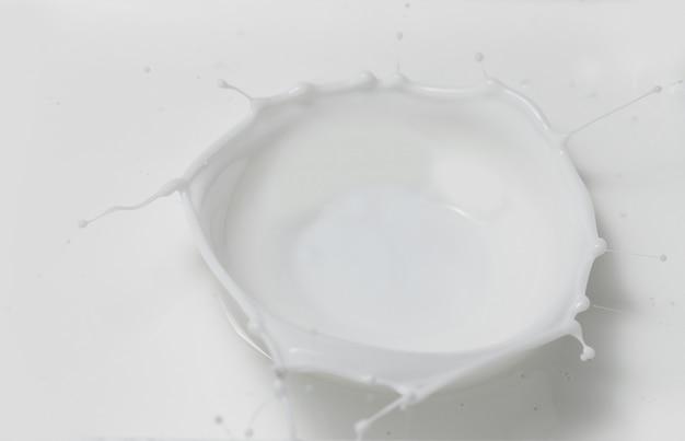Leite fresco derramando fazendo uma coroa espirrar em uma piscina de leite. vista do topo.