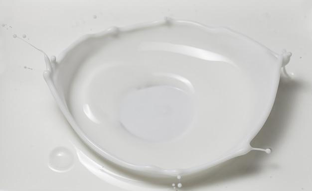 Leite fresco derramando fazendo uma coroa espirrar em uma piscina de leite. vista superior, isolada em cinza-branco
