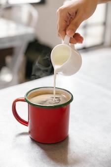 Leite fresco derramando no café quente no copo vermelho com vapor.
