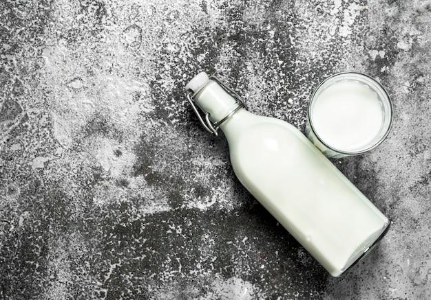 Leite fresco em garrafa na mesa rústica.
