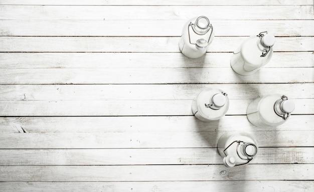 Leite fresco em garrafas na mesa de madeira branca.