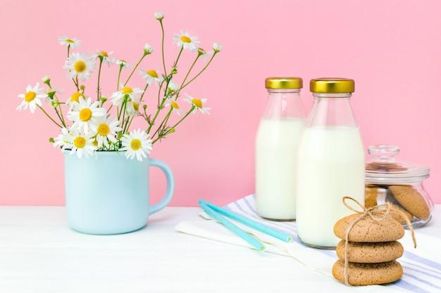 Leite fresco em uma garrafa de vidro e biscoitos caseiros de aveia em branco
