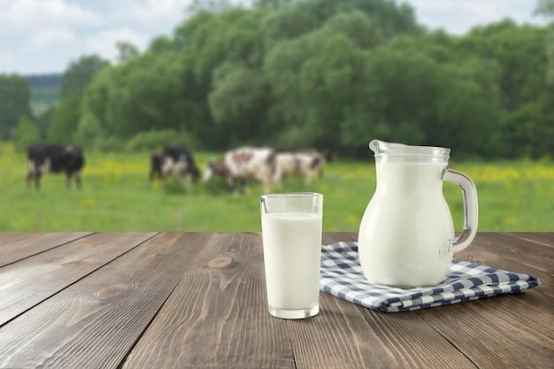 Leite fresco em vidro na mesa de madeira escura e paisagem borrada com vaca no prado. alimentação saudável. estilo rústico.