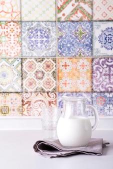 Leite fresco no jarro de vidro e vidro, parede com azulejos coloridos antigos