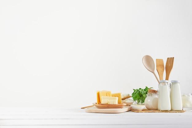 Leite fresco, queijo cottage, creme de leite, queijo, manteiga, ovos, na mesa de madeira. a utilidade do leite, produtos lácteos para adultos e crianças. ainda vida de produtos naturais.
