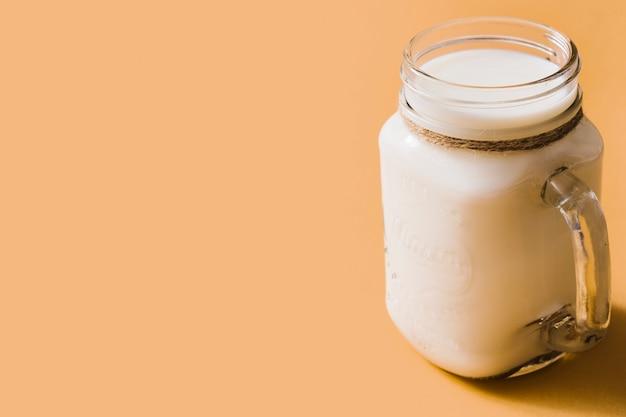 Leite fresco saudável no frasco de vidro com alça sobre o pano de fundo laranja