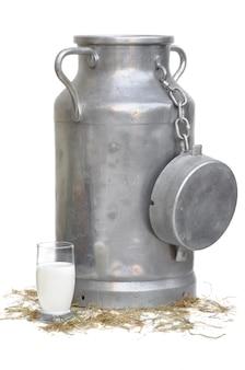 Leite grande pode com um pouco de copo de leite na palha e isolado no branco