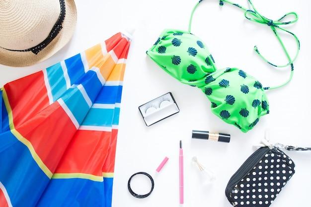 Leite liso da moda de verão com maiô de cor verde, colorido umbella de praia e acessórios de menina no fundo branco