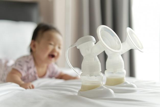 Leite materno nas garrafas da bomba de leite na cama com o bebê de sorriso que rasteja no fundo.