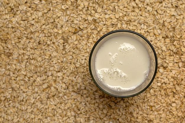 Leite não diário em um copo com aveia integral como fundo desfocado, leite de amêndoa, vista superior