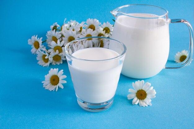 Leite no copo e jarro com flores