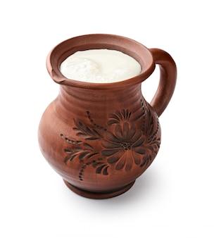 Leite no jarro de barro, isolado no fundo branco