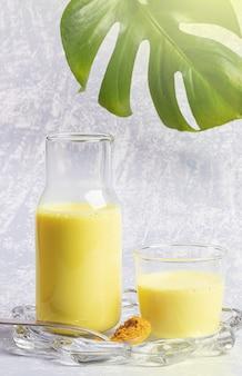 Leite orgânico de açafrão. garrafa e copo com leite dourado no prato transparente. fundo cinza claro, folha de monstera.