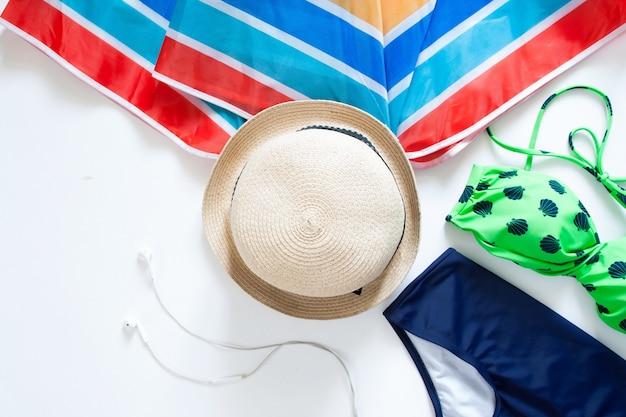 Leite plana de itens de verão, guarda-chuva colorido, chapéu e maiô no fundo branco