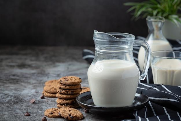 Leite produtos saborosos produtos lácteos saudáveis sobre uma mesa com creme de leite em uma tigela, tigela de queijo cottage, creme em um banco e leite jar, garrafa de vidro e um copo.