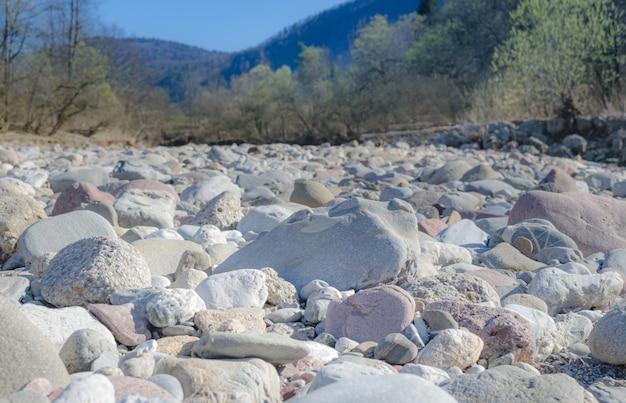 Leito seco do rio cheio de pedras de seixos chamuscados pelo sol