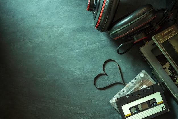 Leitor de cassetes e fone de ouvido no chão de cimento. forma de coração da tira de fita cassete.