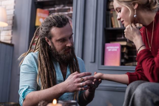 Leitor de palma. homem barbudo positivo olhando para a mão do cliente enquanto trabalhava como quiromante