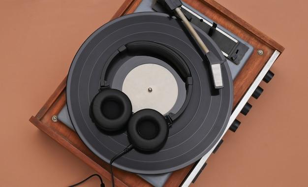Leitor de vinil retrô e fones de ouvido estéreo em um fundo marrom. vista do topo. postura plana