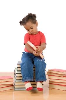 Leitura adorável do bebê africano que senta-se em uma pilha dos livros em um fundo excedente branco
