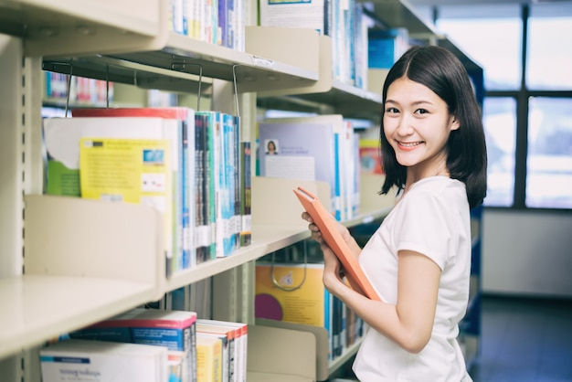 Leitura asiática do estudante na biblioteca na universidade.