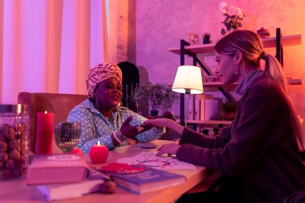 Leitura das mãos. cartomante rechonchudo afro-americano usando um anel enorme e lendo a palma da mão do cliente
