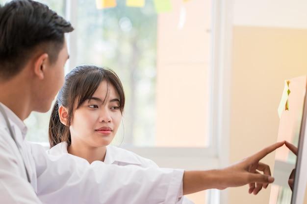 Leitura do jovem médico asiático, verificando informações no computador, explicar os resultados das boas notícias do tratamento para a sala de exame de pacientes do sexo feminino com o uso de estetoscópio. conceito médico de saúde