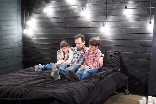 Leitura familiar da noite. pai lê as crianças um livro antes de ir para a cama