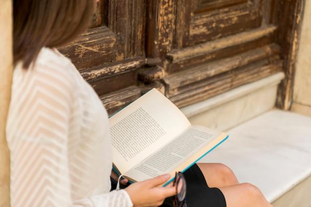 Leitura feminina perto de portas de madeira