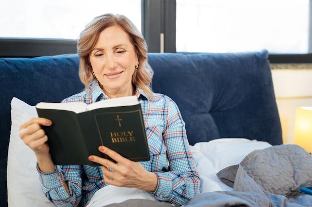 Leitura pensativa. mulher madura curiosa atenta lendo livro sagrado durante sua rotina matinal diária