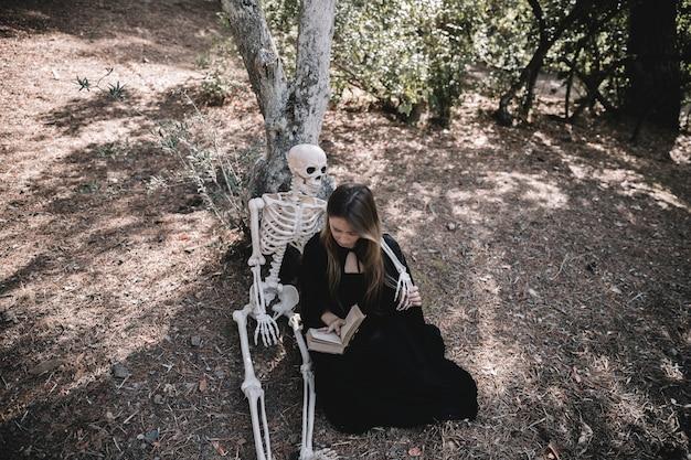 Leitura, senhora, em, bruxa, roupas, abraçando, esqueleto