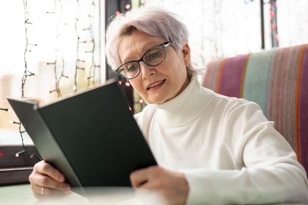 Leitura sênior da mulher do baixo ângulo