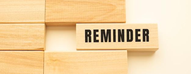 Lembrete o texto em uma tira de madeira sobre uma mesa branca.
