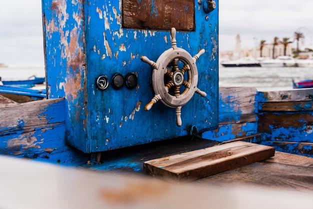 Leme de madeira pequeno de um barco encalhado envelhecido e abandonado na costa do mar.
