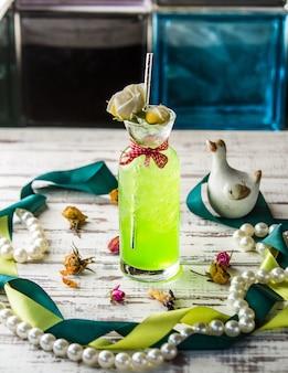 Lemonadr verde limão em uma jarra de vidro sobre uma mesa de madeira.