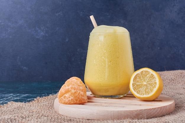 Lemonnd tangerinas com um copo de bebida em azul.