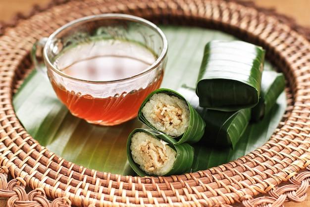 Lemper ayam servido com chá. lemper é um lanche indonésio feito de arroz glutinoso recheado com frango ralado temperado e embrulhado em folha de bananeira